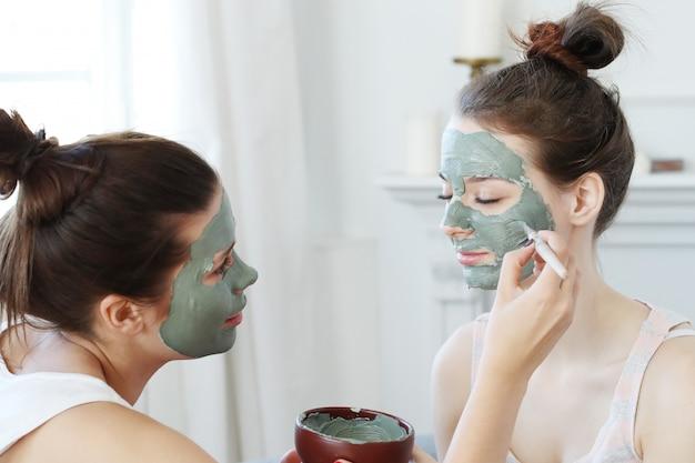 Vrouw die een gezichtsmasker toepast op haar vriend, het concept van de huidzorg