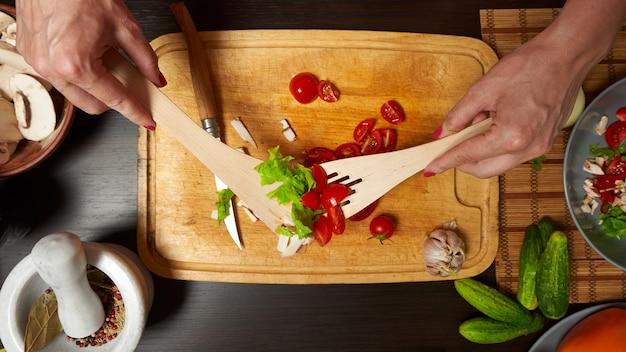 Vrouw die een gezonde salade in de keuken mengt