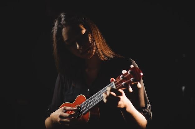 Vrouw die een gitaar in muziekschool speelt