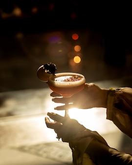 Vrouw die een glas cocktail in zonsondergang houdt