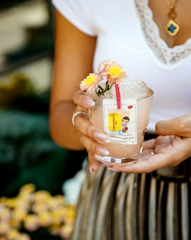 Vrouw die een glas drank met ijs houdt dat met voering van liefdeisgum wordt verfraaid