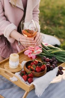 Vrouw die een glas met wijn houdt bij een picknick