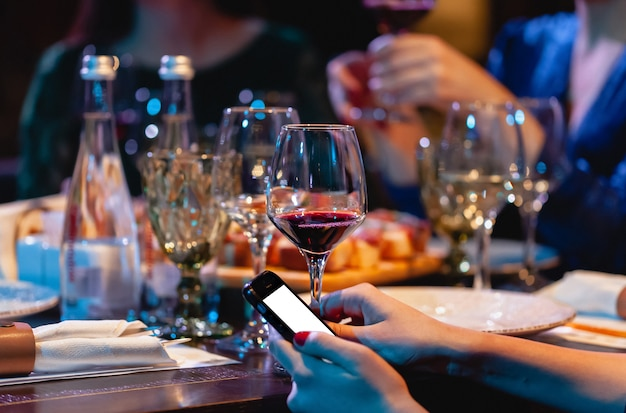 Vrouw die een glas rode wijn en telefoon houdt. diner in het restaurant, feest