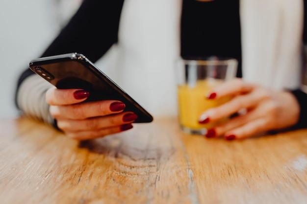 Vrouw die een glas sap heeft en haar telefoon controleert