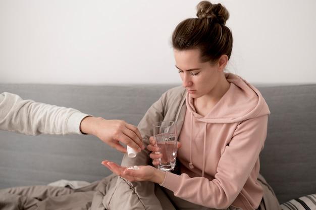 Vrouw die een glas water en pillen houdt