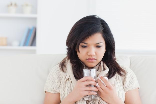 Vrouw die een glas water houdt terwijl het koud is