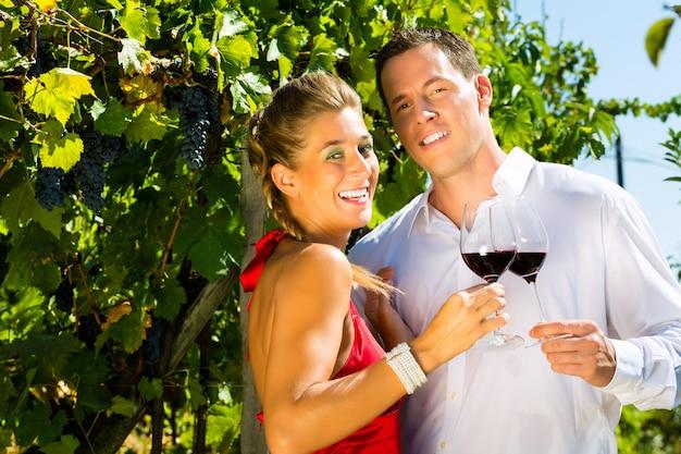 Vrouw die een glaswijn in hand houdt, man binnen