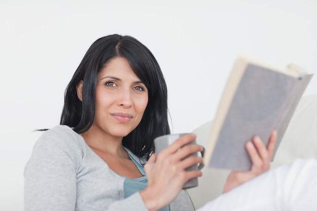 Vrouw die een grijze mok en een boek houdt