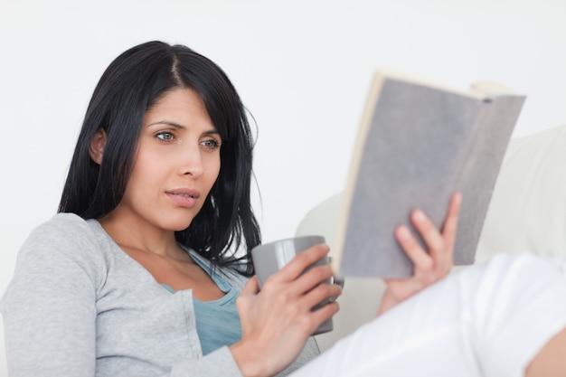 Vrouw die een grijze mok houdt terwijl het lezen van een boek