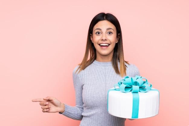 Vrouw die een grote cake over geïsoleerde roze muur houdt verrast en vinger aan de kant richt