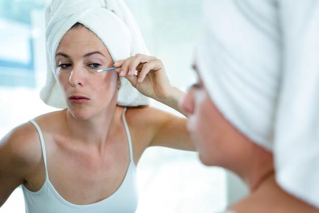 Vrouw die een haarhanddoek draagt met een wattenstaafje om haar mascara te repareren