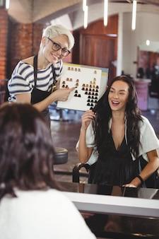 Vrouw die een haarkleur met stilist selecteert