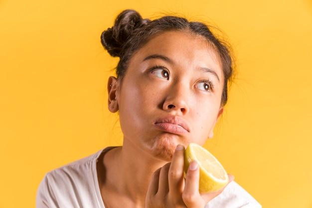Vrouw die een halve citroen houdt en weg kijkt