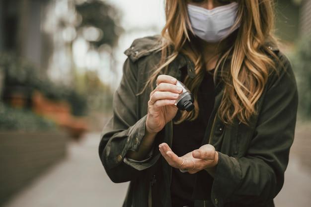 Vrouw die een handdesinfecterend middel gebruikt tijdens een pandemie van het coronavirus