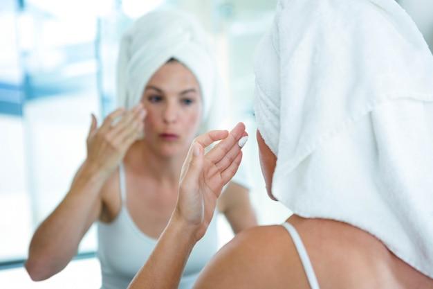 Vrouw die een handdoek op haar haar draagt, past gezichtscrème toe in de spiegel