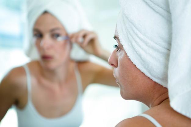 Vrouw die een handdoek op haar hoofd draagt en mascara toepast
