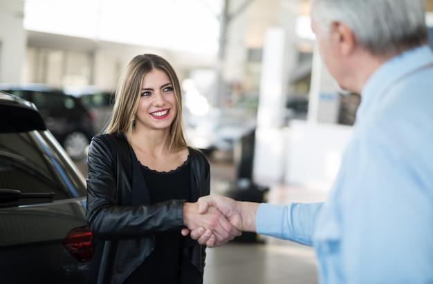 Vrouw die een handdruk geeft om de overeenkomst voor haar nieuwe auto te verzegelen