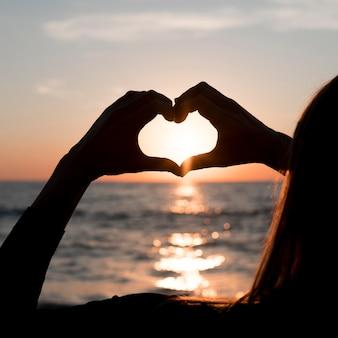 Vrouw die een hart maakt bij zonsondergang