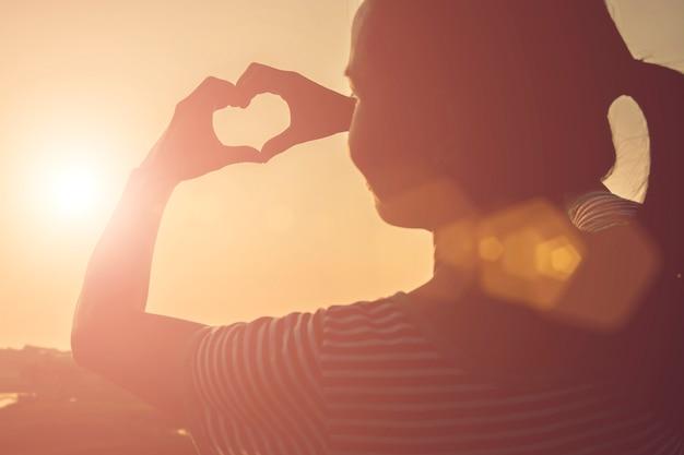 Vrouw die een hart met haar handen