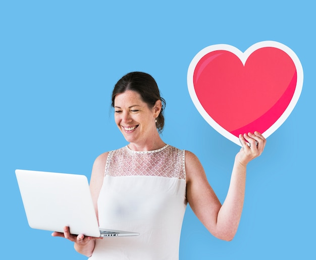 Vrouw die een hartpictogram toont en laptop met behulp van