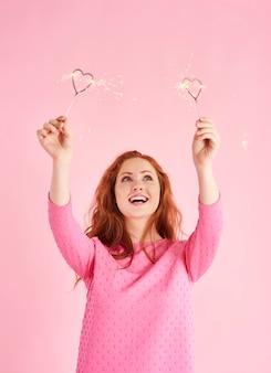 Vrouw die een hartvormig sterretje vasthoudt en omhoog kijkt naar de studio