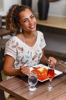 Vrouw die een heerlijk gerecht van vlees en noedels parmigiana eet.