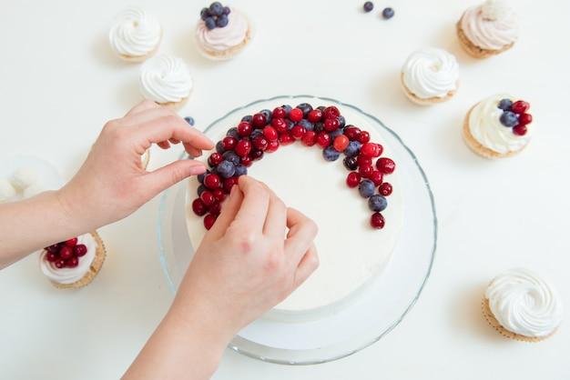 Vrouw die een heerlijke cake met bosbessen verfraait