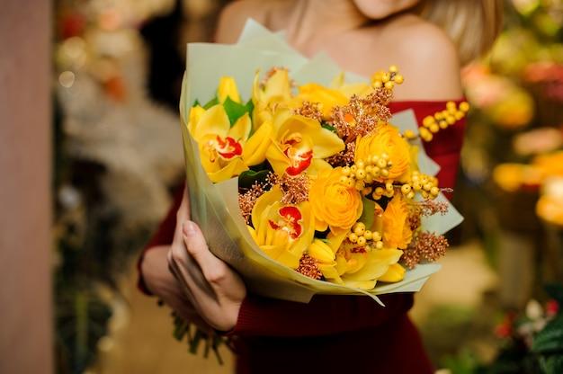 Vrouw die een helder geel bloemboeket houdt voor de dag van valentine
