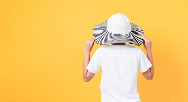 Vrouw die een hoed op oranje achtergrond draagt