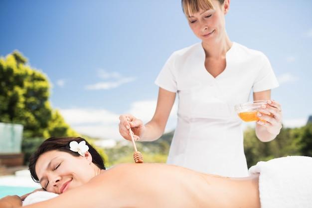 Vrouw die een honingsmassage van masseur dichtbij pool ontvangt