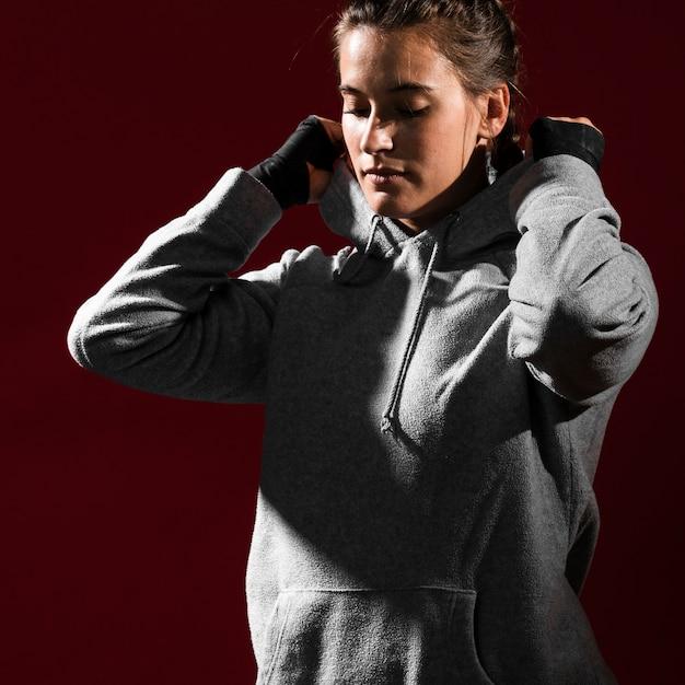 Vrouw die een hoodie draagt en haar ogen heeft gesloten