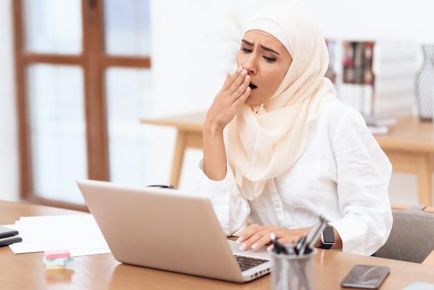 Vrouw die een hoofddoekzitting draagt die op het werk wordt vermoeid.