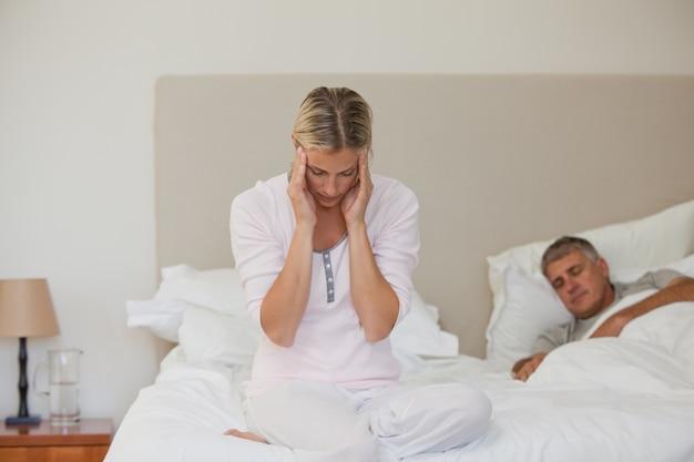 Vrouw die een hoofdpijn heeft terwijl haar echtgenoot slaapt