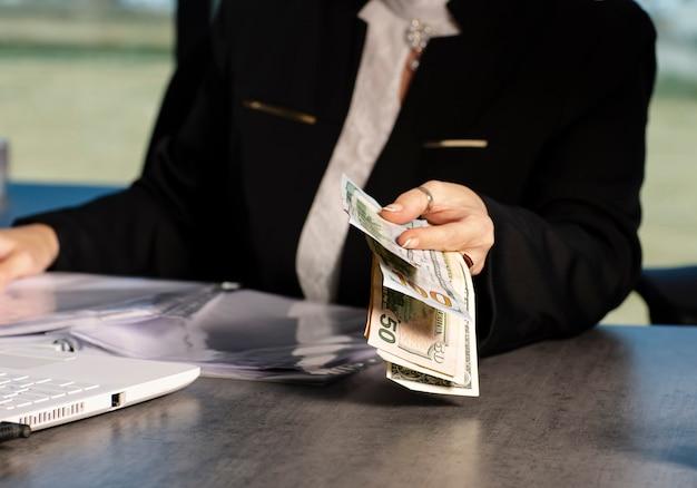 Vrouw die een hoop geldbankbiljetten geeft, geld terug