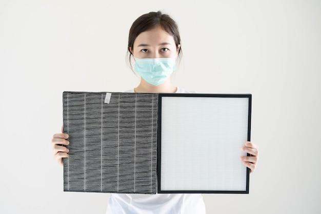 Vrouw die een hygiënisch beschermend gezichtsmasker draagt tijdens het vervangen van een vuil luchtfilter