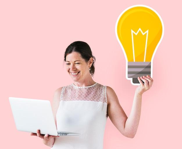 Vrouw die een ideepictogram houdt en laptop met behulp van