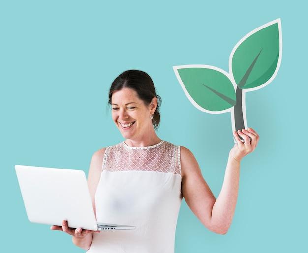 Vrouw die een installatiepictogram houdt en laptop met behulp van