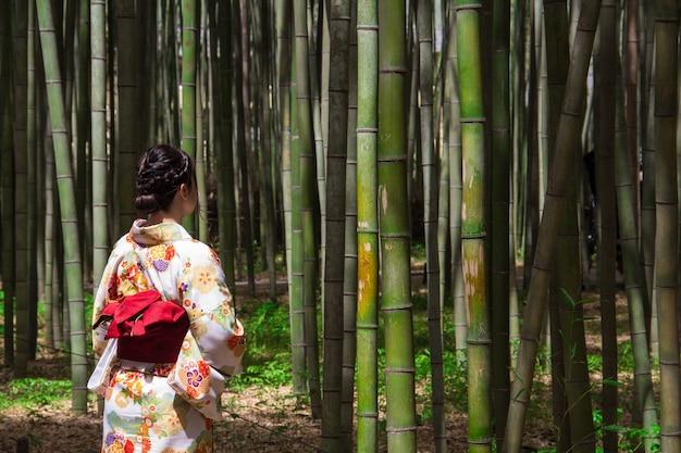 Vrouw die een japans traditioneel kimono-kledingstuk draagt en in een bamboebos staat