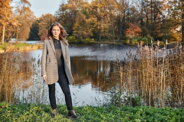Vrouw die een jas draagt en zich in park bevindt