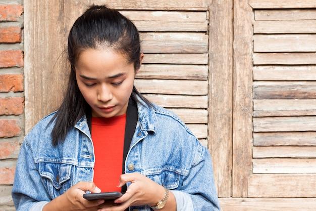 Vrouw die een jasje draagt en met mobiele telefoon speelt