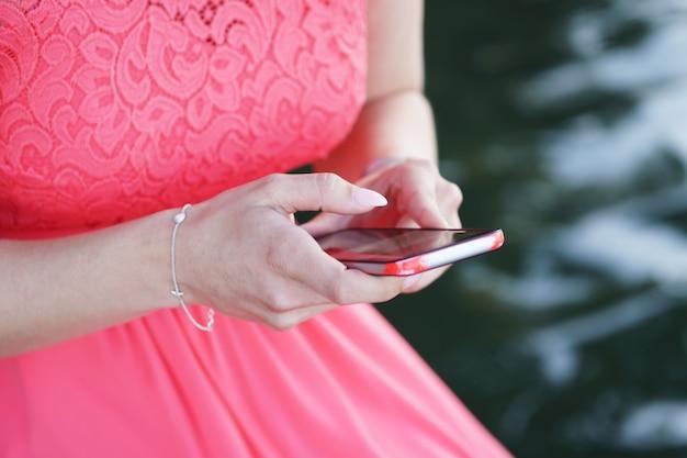 Vrouw die een jurk draagt en een smartphone vasthoudt