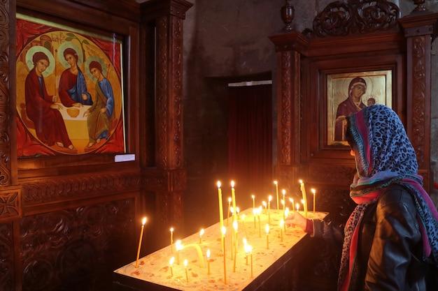 Vrouw die een kaars aanbiedt in de historische kerk van het jvari-klooster mtskheta town georgia
