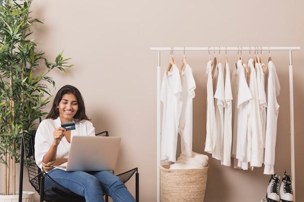 Vrouw die een kaart houdt en aan laptop werkt