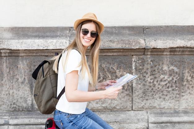 Vrouw die een kaart houdt en camera bekijkt