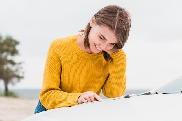 Vrouw die een kaart op haar auto leest