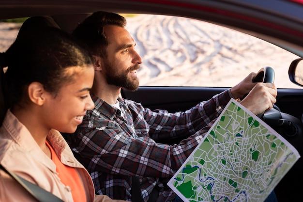 Vrouw die een kaart voor een nieuwe bestemming in de auto controleert