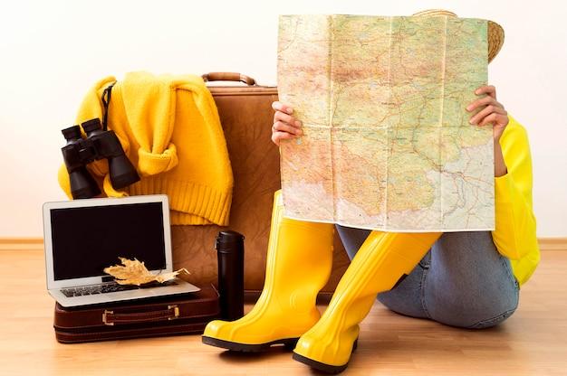 Vrouw die een kaart voor een reisbestemming in de herfst controleert