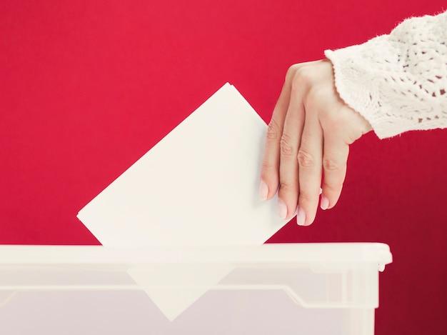 Vrouw die een kaartmodel in een doos voor verkiezing zet