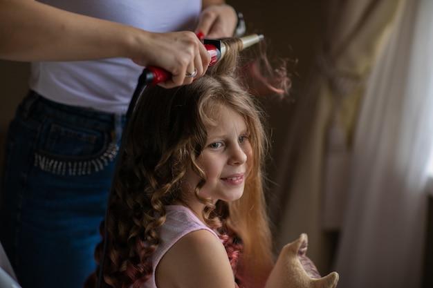 Vrouw die een kapsel door krullend ijzer maken aan jong leuk meisje met lang haar binnen. krullende stijl.