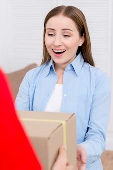Vrouw die een kartondoos ontvangt en gelukkig is